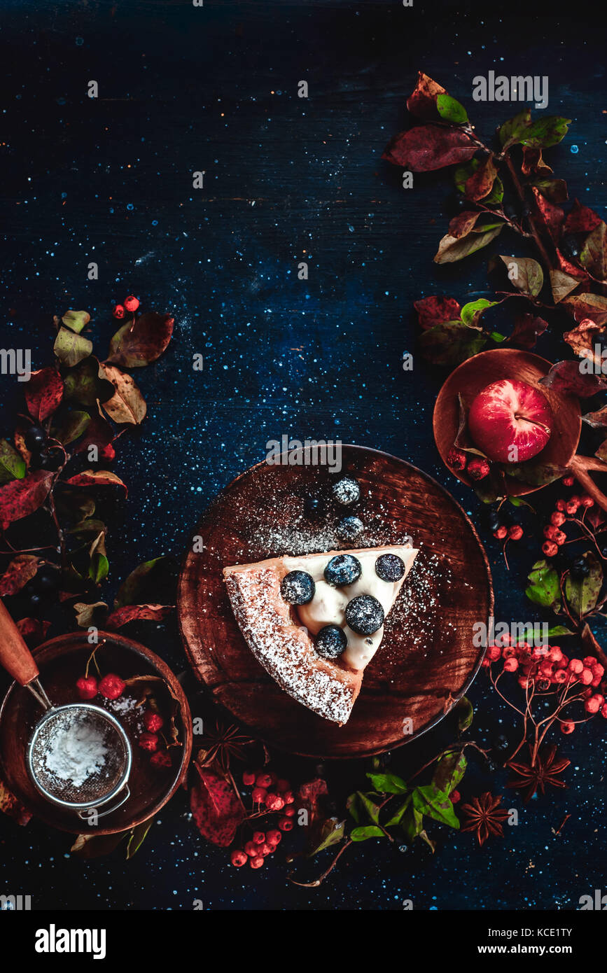 A piece of pumpkin pie with blueberries and persimmon on a dark wooden background with floral decoration. Autumn - Stock Image