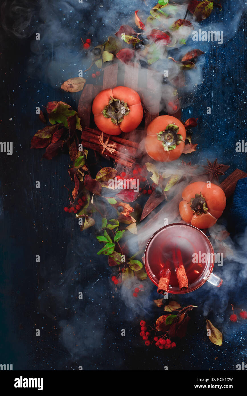 Dark autumn still life ripe persimmons, hot tea and floral decoration on a background with leaves and smoke. Conceptual - Stock Image