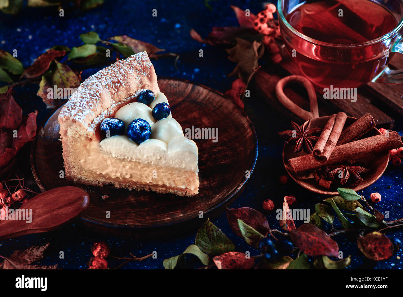 Hommemade crust cake with wipped cream, blueberries and pumpkin puree on a dark background with leaves and cinnamon. - Stock Image