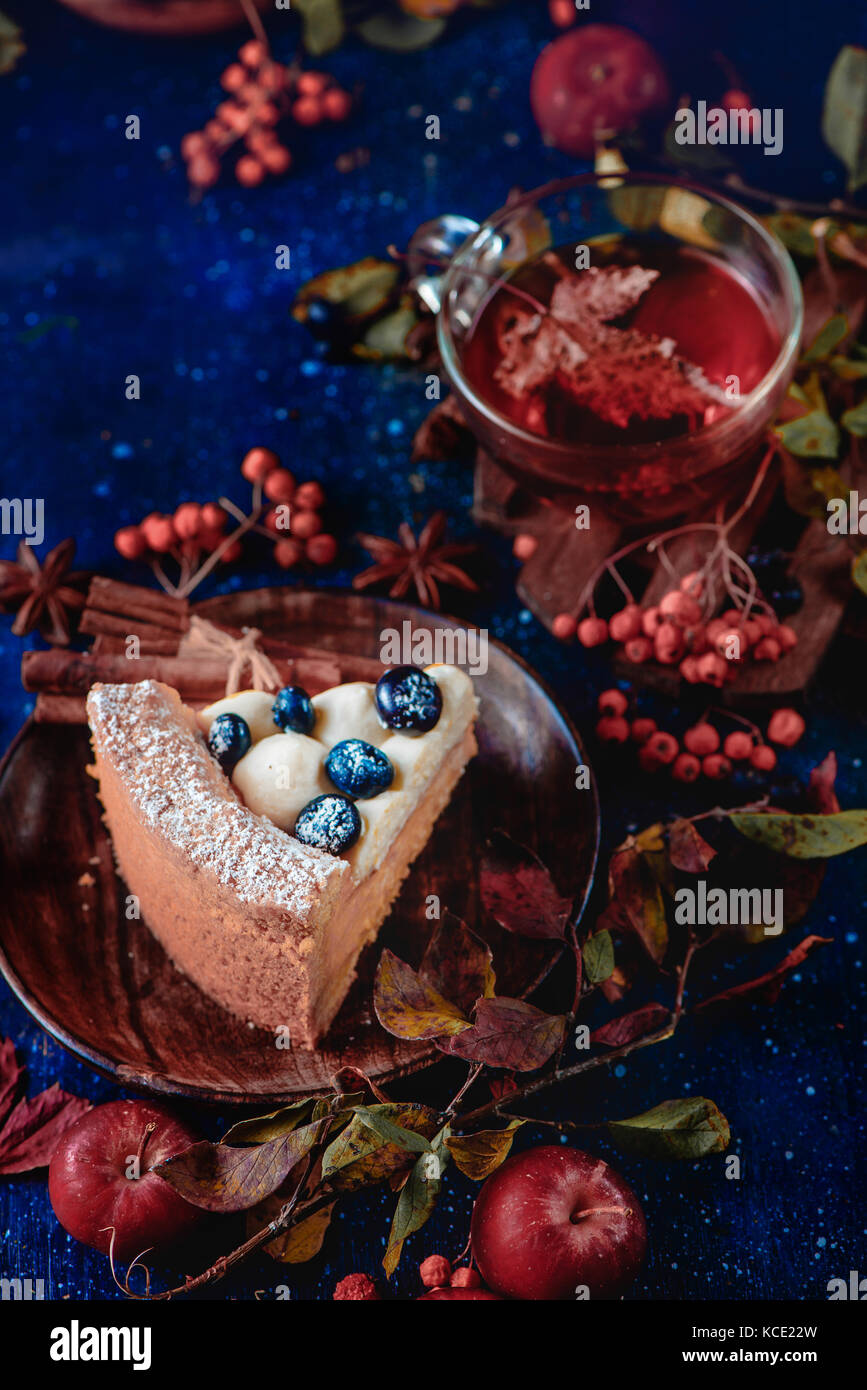 Close-up of a piece of pumpkin pie with powdered sugar in a dark autumn still life with smoke. Sweet Halloween concept - Stock Image
