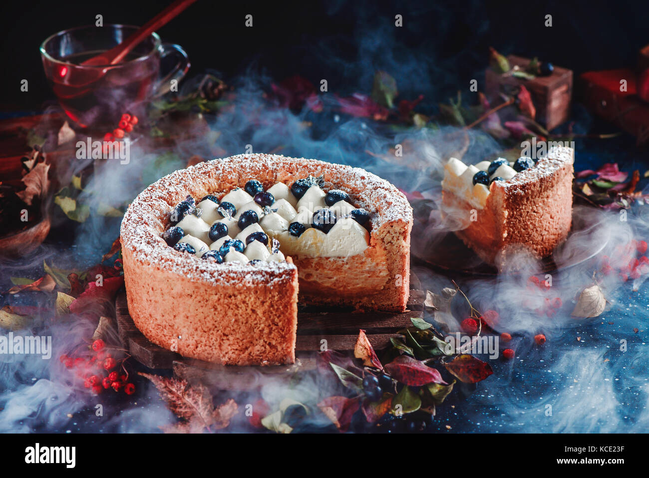 Cut cake with a shortbread crust on a dark background. A piece of cake with whipped cream and blueberries. Traditional - Stock Image