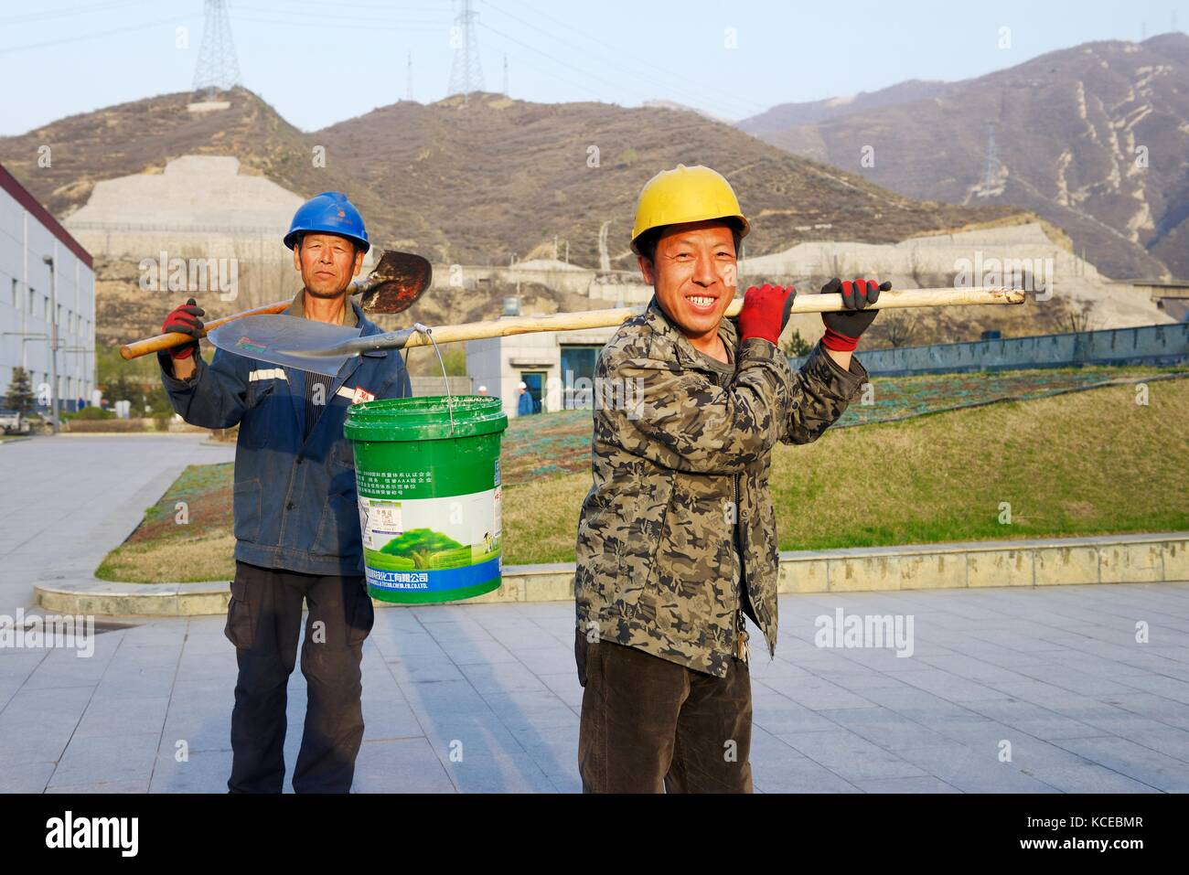 Labourers workmen at end of shift at ultra modern coal fired 1,320 megawatt power plant of Tonghua Xuangang Power - Stock Image