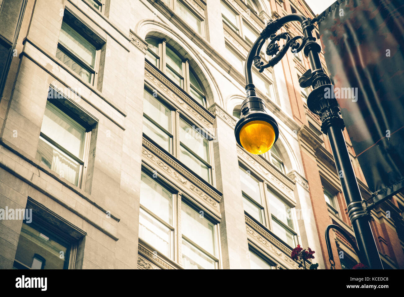 Vintage style illuminated streetlamp with New York City apartment buildings in the background. - Stock Image