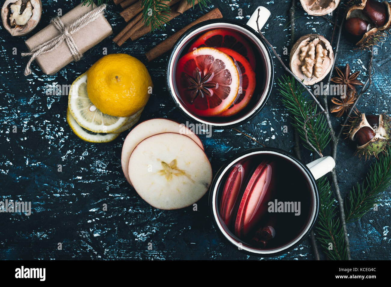 Mulled wine with apple and lemon  slices in white rural mugs  on rustic table , top view - Stock Image