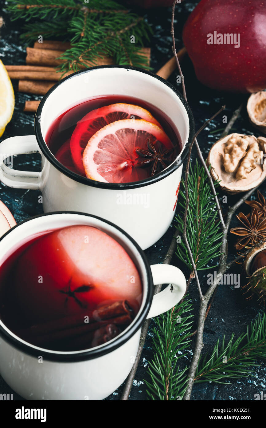 Mulled wine with apple and lemon  slices in white rural mugs  on rustic table - Stock Image