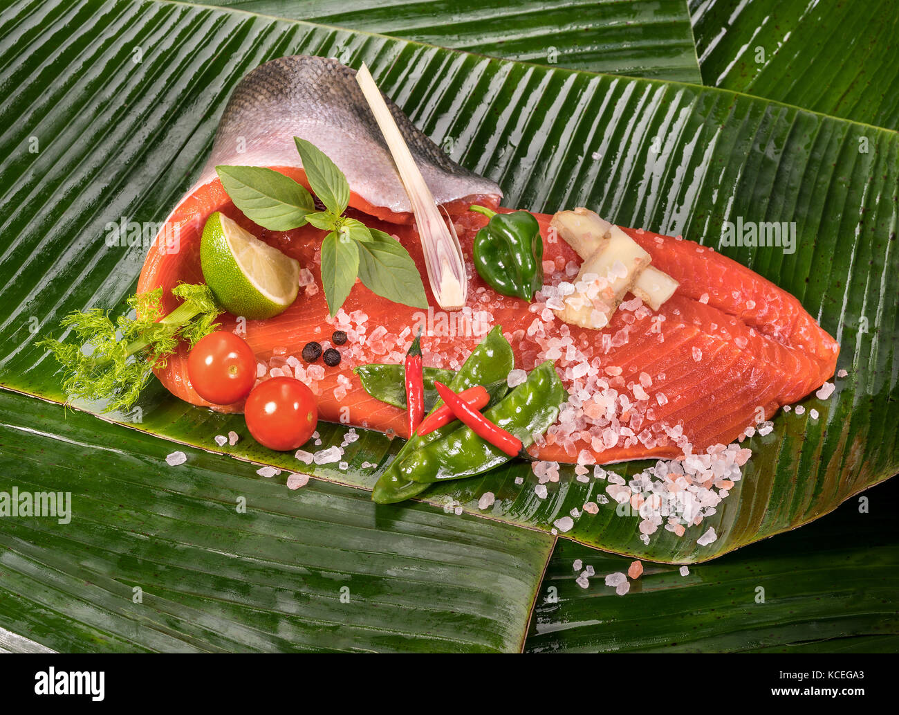 fresh sockeye wild salmon and ingredients for steaming in the banana leaf - Stock Image