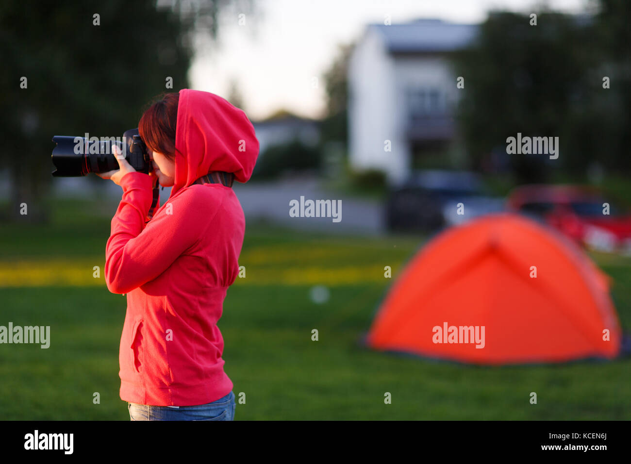 Girl photographer near of tent camp - Stock Image
