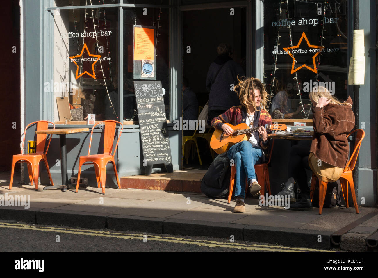 Young couple sit in sun at a table outside The Fossgate Social coffee shop & bar, York, England, UK. The man - Stock Image