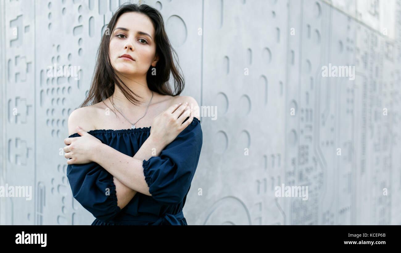 Beautiful brunette standing by gray modern wall - Stock Image