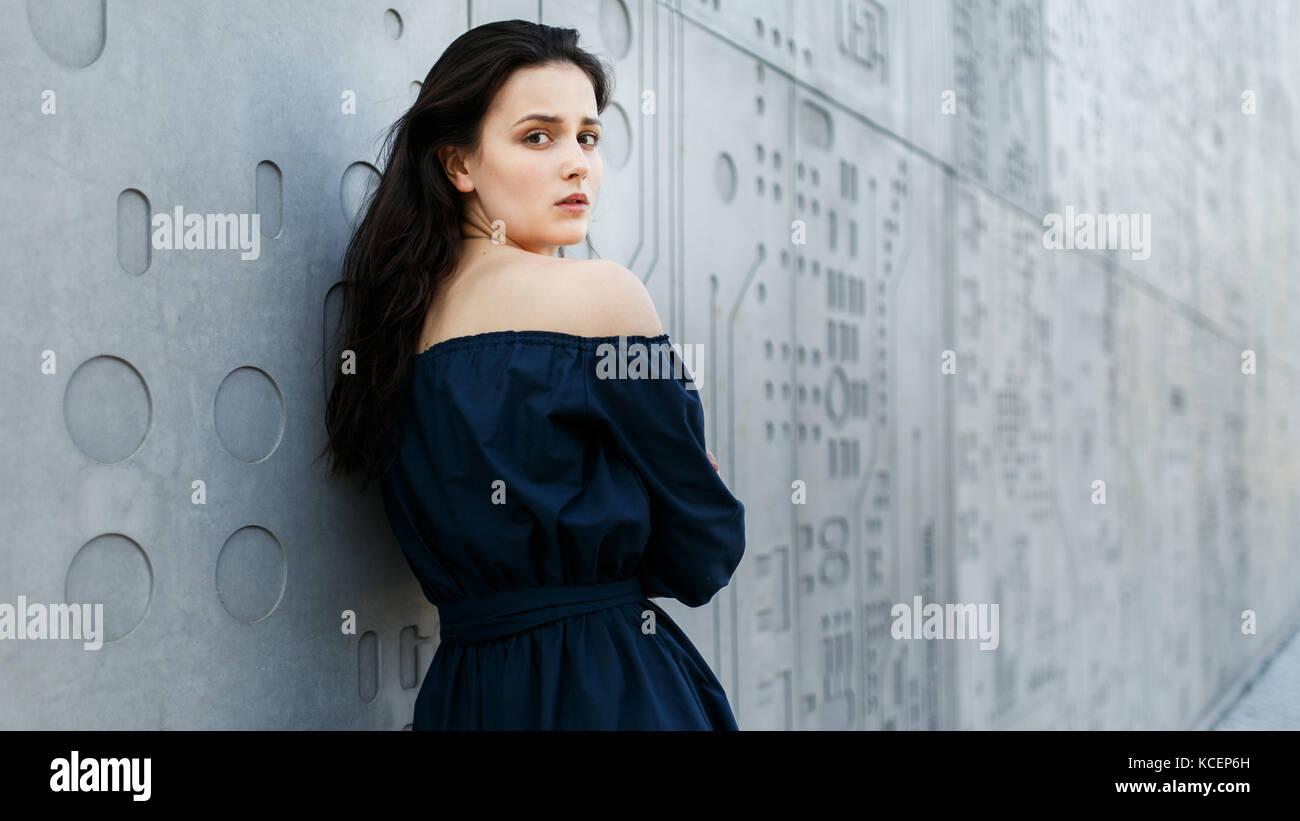 Beautiful woman standing by gray modern wall - Stock Image