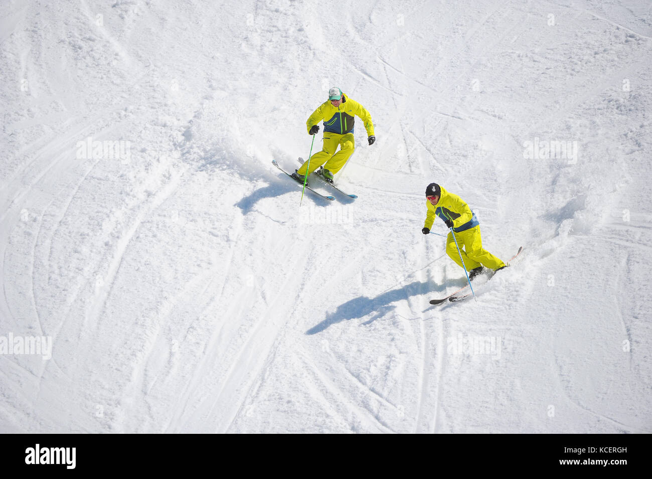 Two skiers carve turns photographed from above. - Stock Image