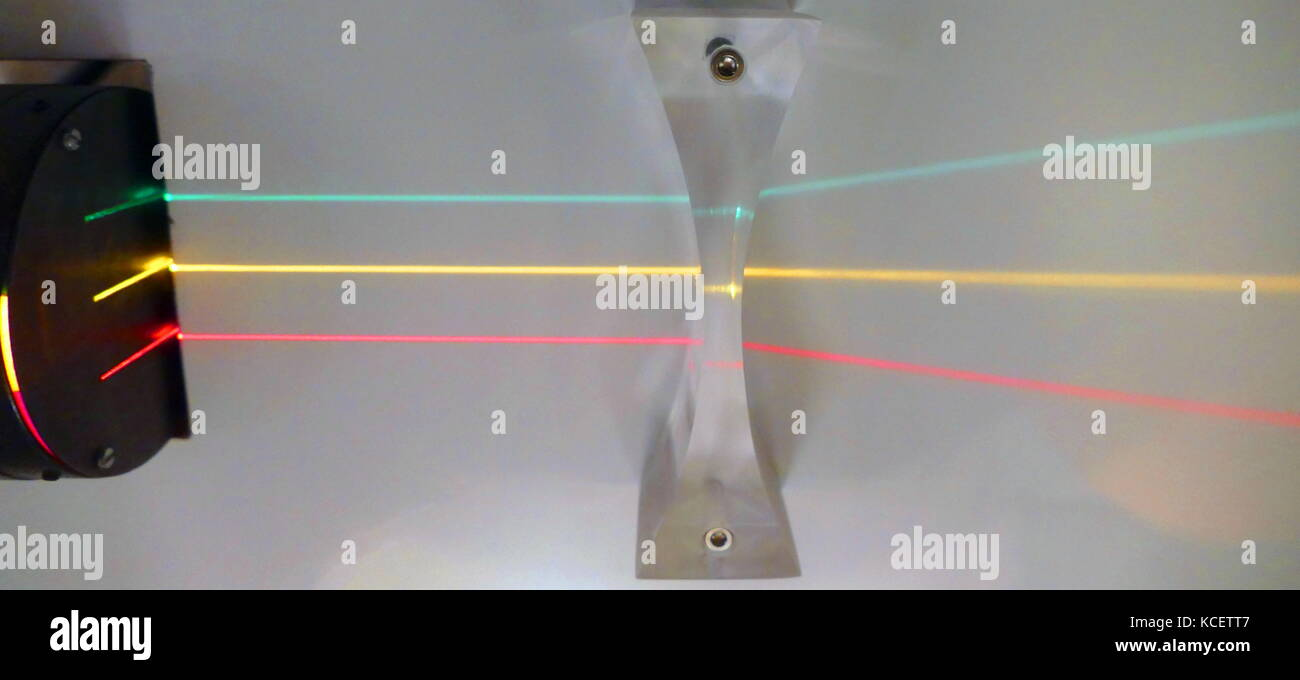 three parallel beams of light are refracted through a concave Lens. A concave lens is thinner at the centre than Stock Photo