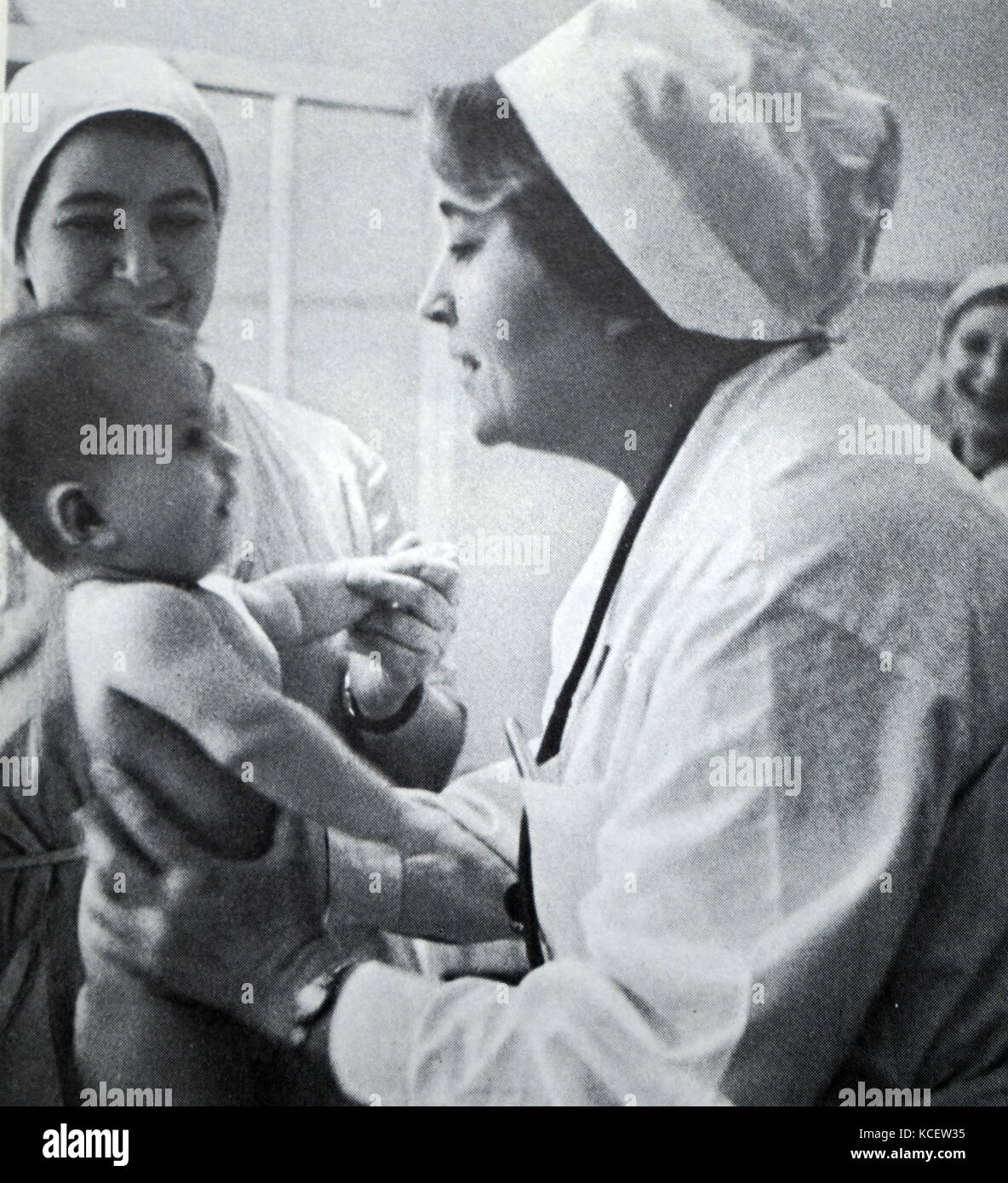 Soviet Russian paediatrician and nurse examine a baby at a hospital. Moscow circa 1960 - Stock Image