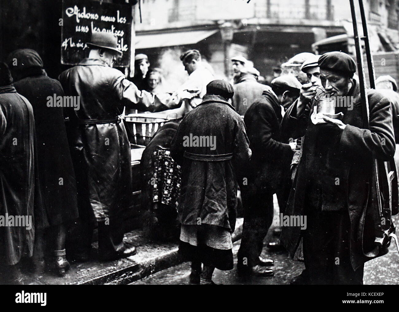 Photograph of a French soup kitchen distributes food to hungry people, in Paris, during the German occupation 1941. - Stock Image