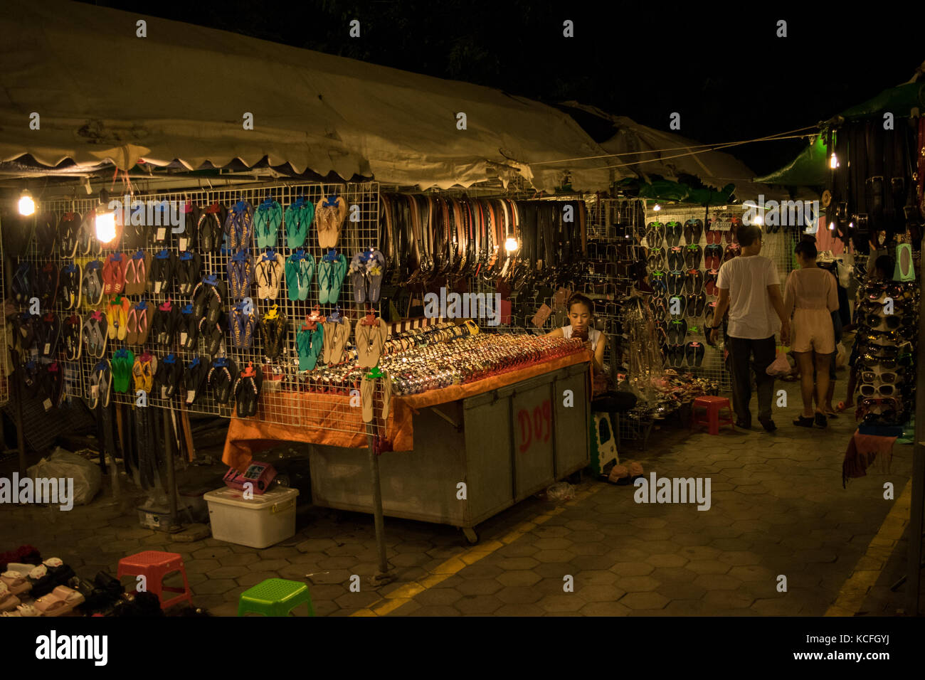 A stall at Phnom Penh night market, selling different accessories such as belts, flip flops and watches. Waiting - Stock Image