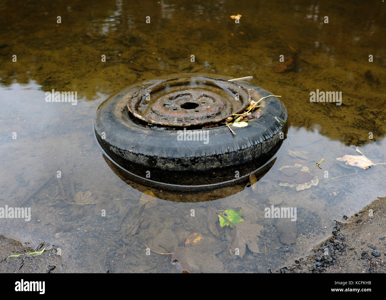 Car tyre and wheel thrown away in river irwell in burrs country park bury lancashire uk - Stock Image