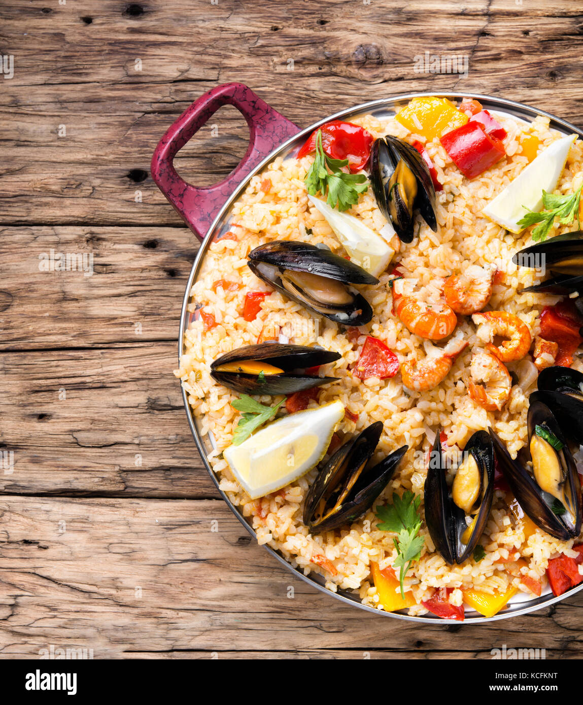 vegetable paella with seafood on wooden background Stock Photo