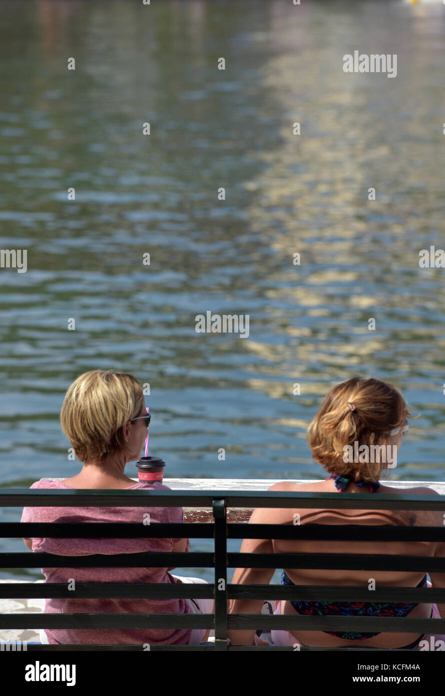 two young women sitting on a bench in kassiopi, Greece looking put to sea next to the harbour chatting. - Stock Image