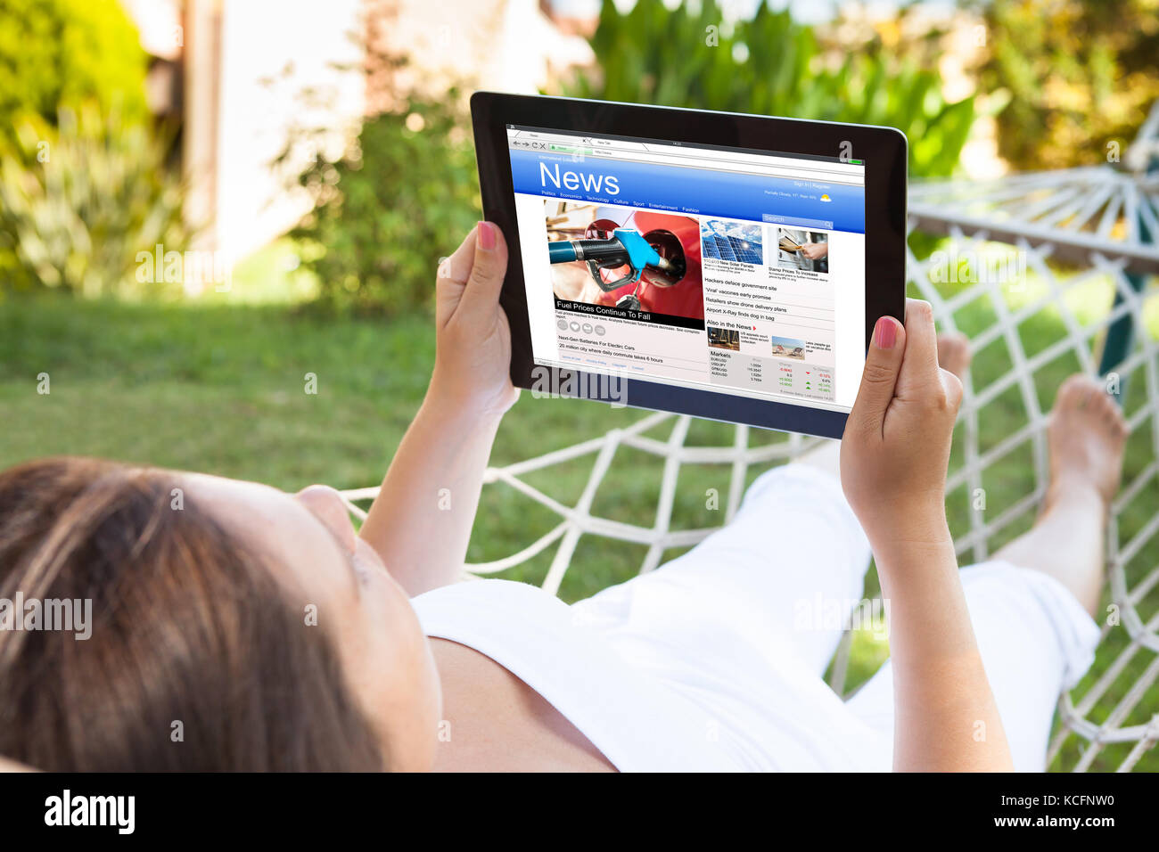 Close-up Of Woman On Hammock Reading News On Her Digital Tablet - Stock Image