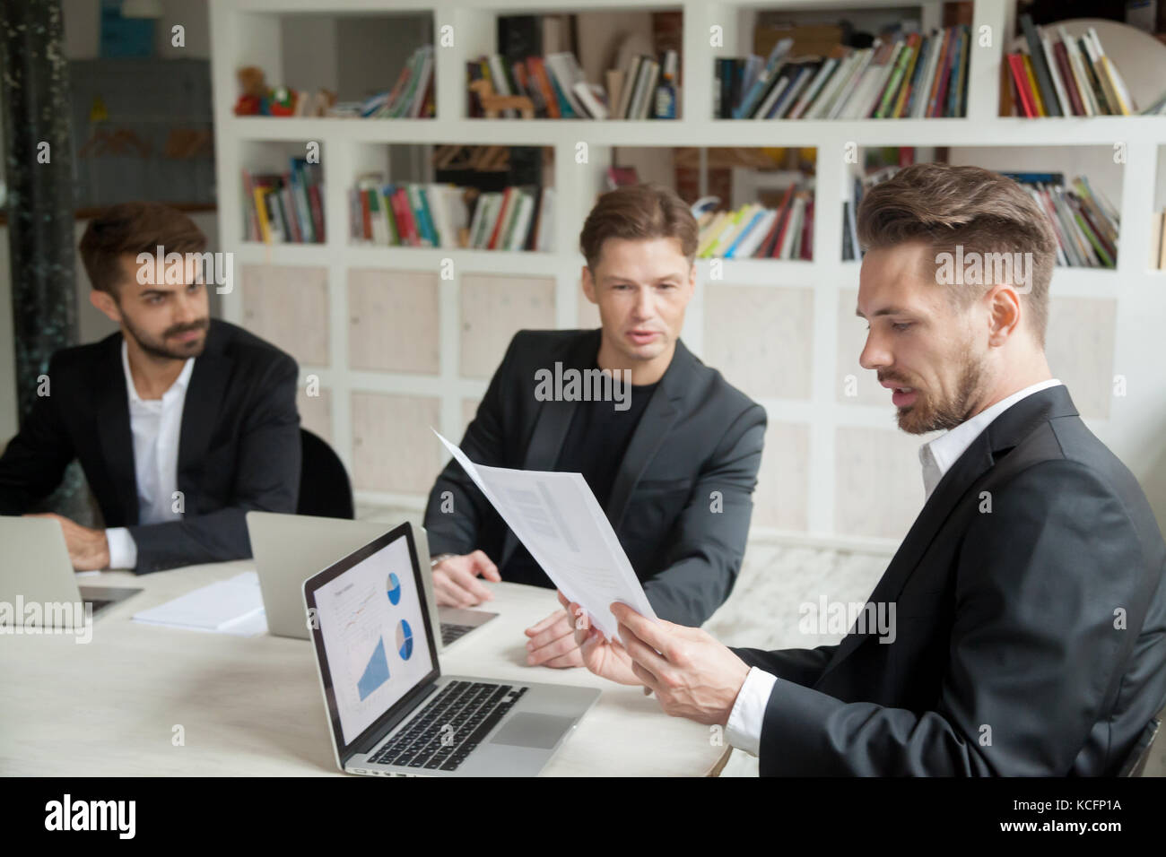 Skeptical boss looking at financial stats report presented by employee. Manager not sure if results are satisfying, - Stock Image