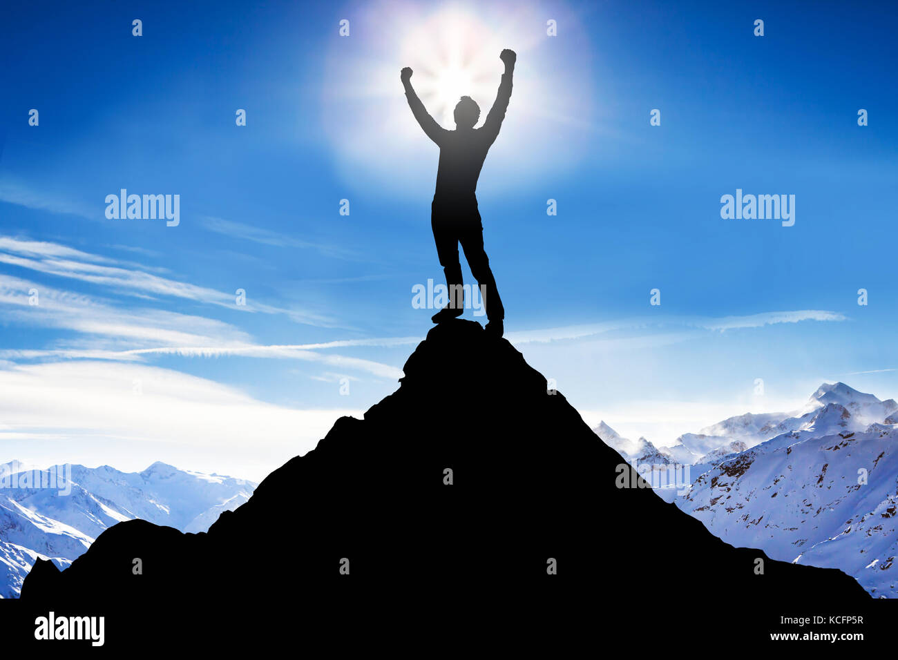 Silhouette Of A Man After Succeeded Climbing Against Snowy Mountains - Stock Image