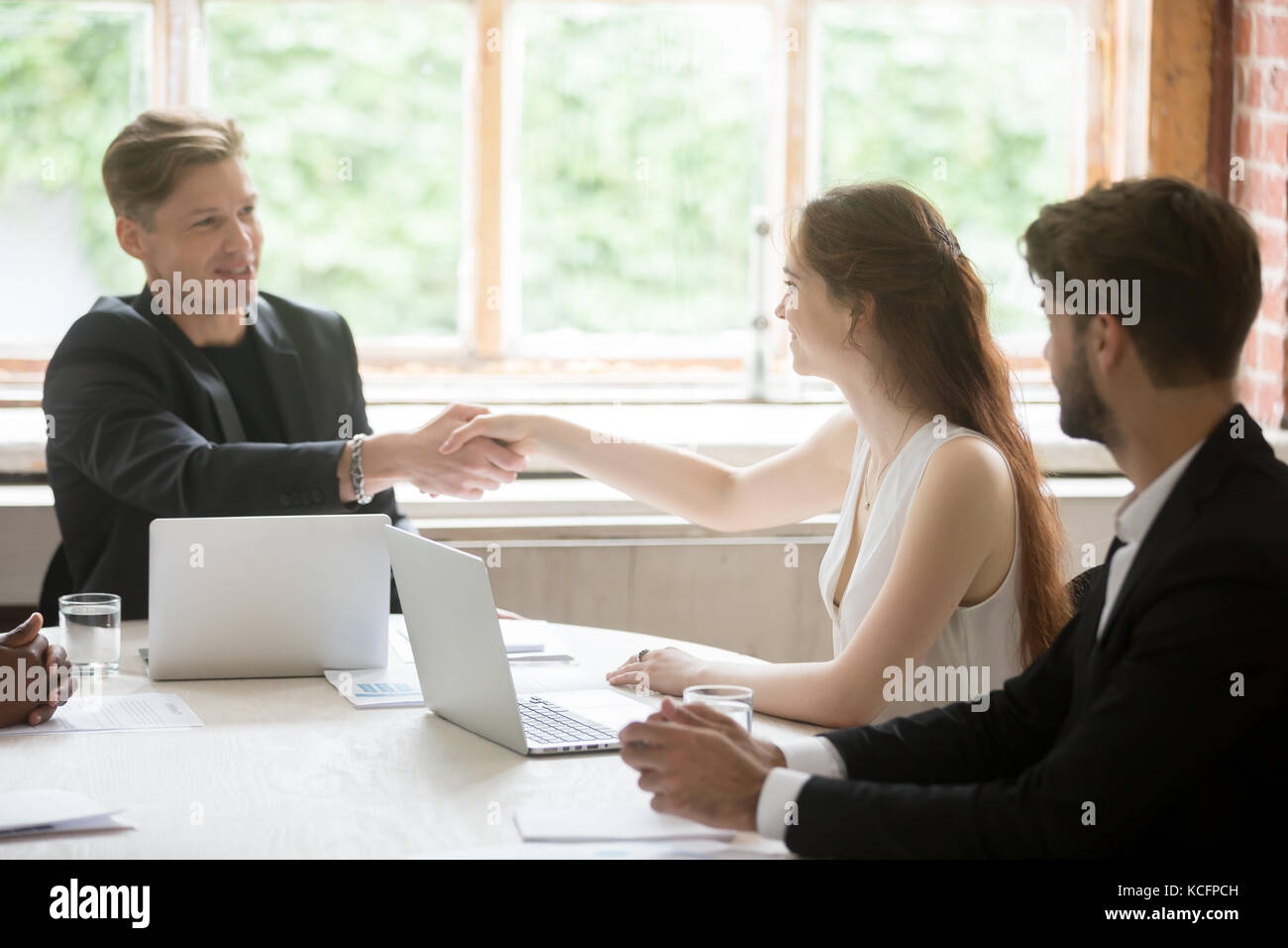 Young male executive in formal suit shaking hands with attractive female coworker. Employees greeting each other - Stock Image