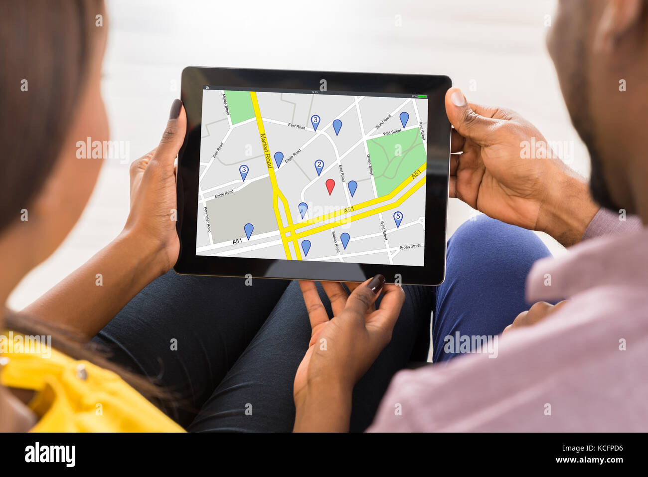 Close-up Of Couple Holding Digital Tablet Showing GPS Map With Navigation Pointers - Stock Image