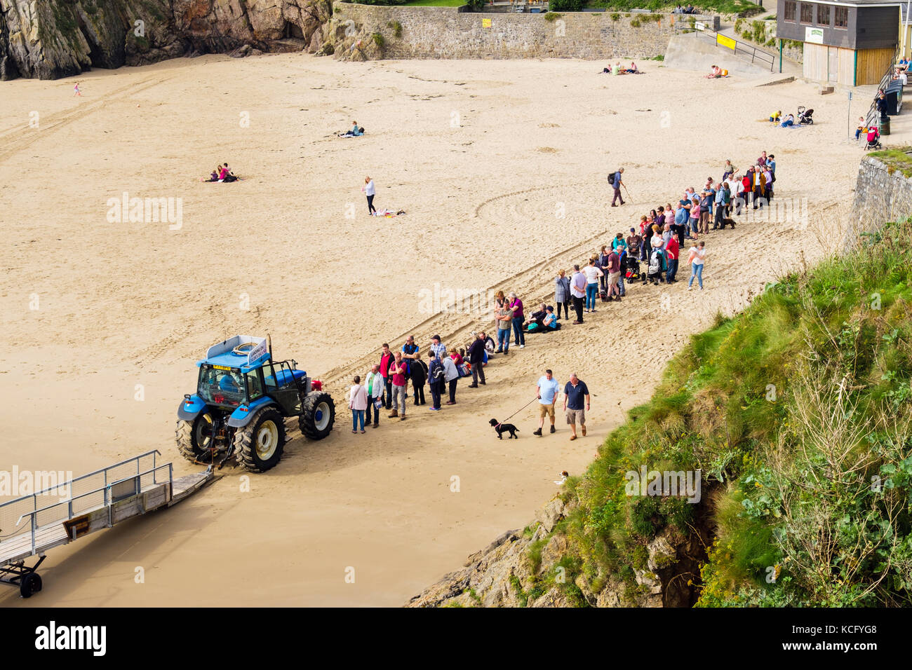 Long queue of people queueing by jetty tractor on Castle beach for boat trip to Caldey Island. Tenby, Pembrokeshire, Stock Photo