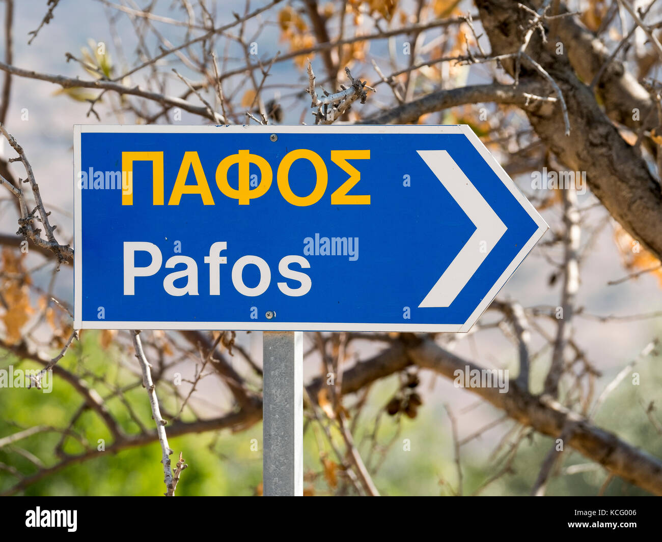 Road sign in the village of Episkopi written in English and Greek showing the direction of Pafos town in the Republic - Stock Image
