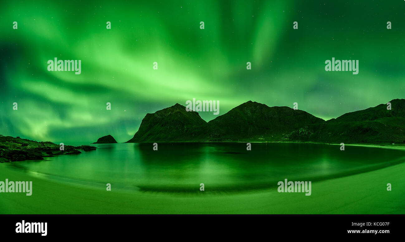 Beach in the Lofoten islands in Norway with strong green norther lights - Stock Image