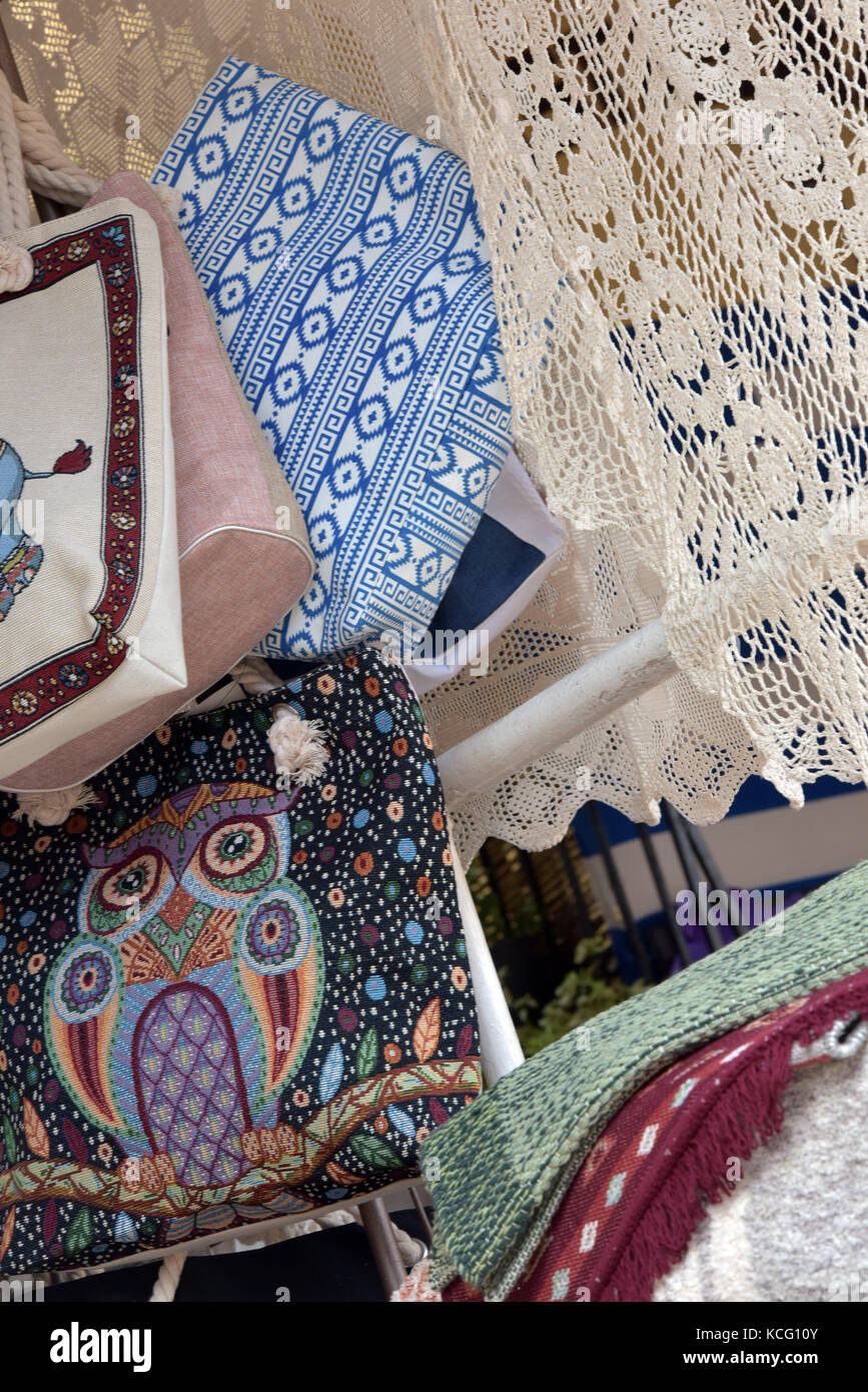 Lace and woven fabrics and materials for sale at a Greek souvenir or textiles shop. Tablecloths and curtains, towels - Stock Image