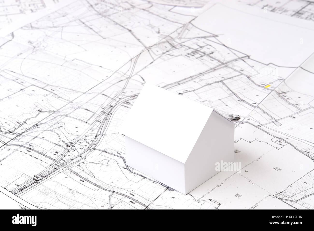 White Little Cardboard House Model On Building Plan Stock