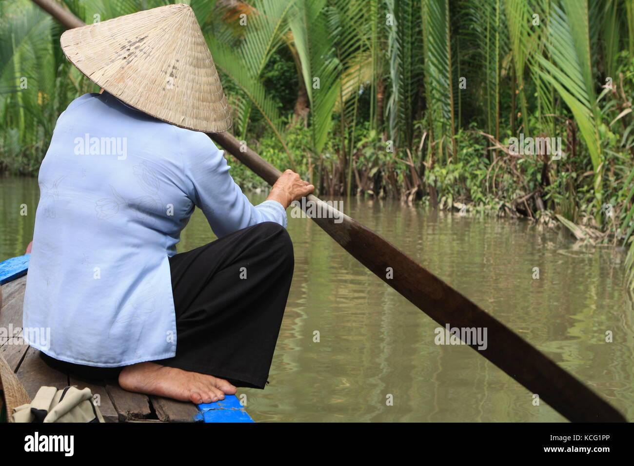 Frau auf Boot beim Rudern in Vietnam - Woman on boat while rowing in Vietnam Stock Photo