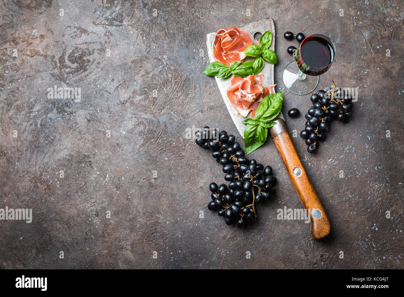 Sliced jamon with butcher knife, grapes and wine. Parma ham hamon on wooden background with copy space, top view. - Stock Image