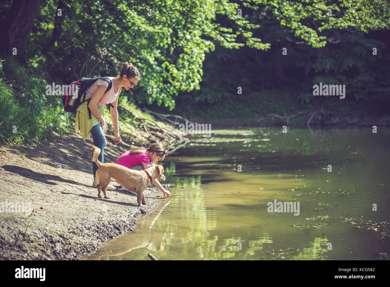 Mother and daughter with dog resting by the lake - Stock Image