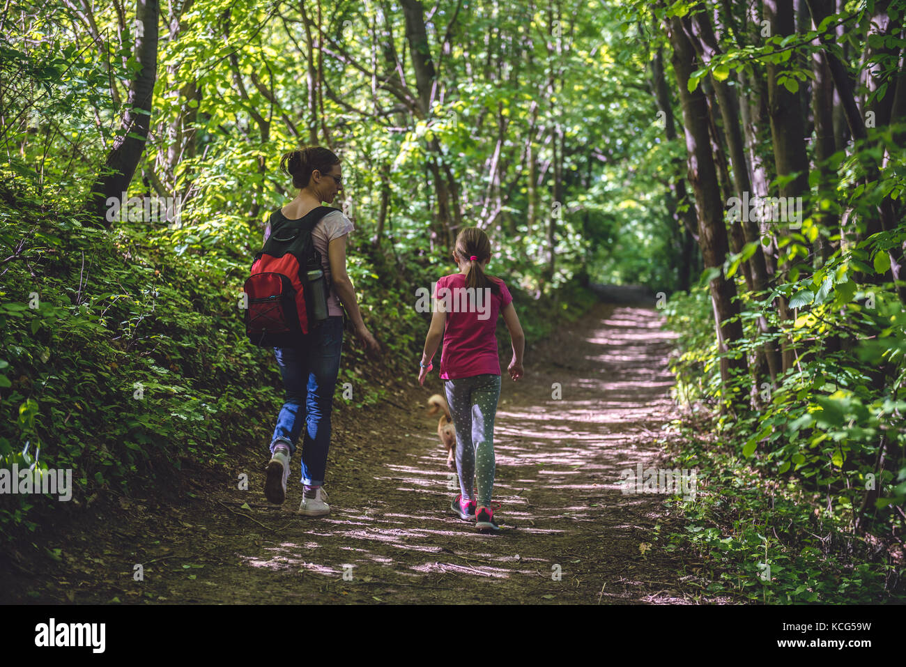 Mother and daughter walking on path in woods and talking - Stock Image