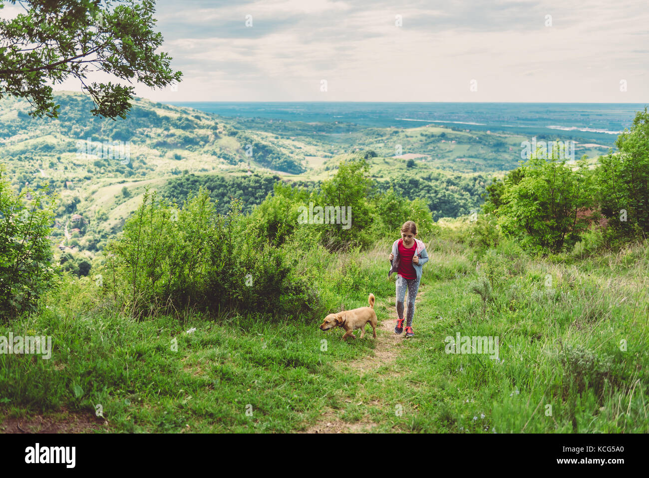 Girl and her dog walking along a hiking trail - Stock Image