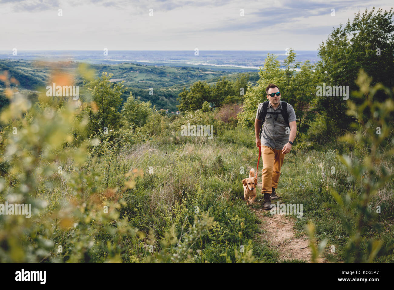 Man with a dog walking along a hiking trail on the mountain - Stock Image