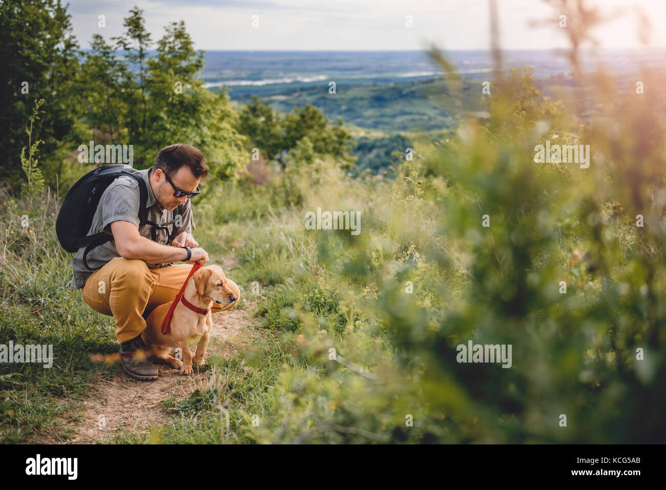 Man wearing sunglasses with a small yellow dog resting at the hiking trail - Stock Image