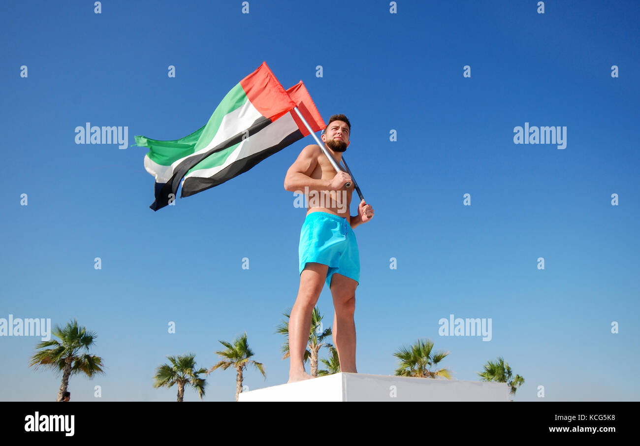 Man holding two UAE flags against the blue sky Celebration of National Day - Day of the United Arab Emirates concept Stock Photo