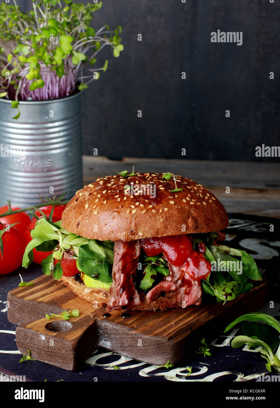 Fresh meat Burger with greens on wooden Board - Stock Image