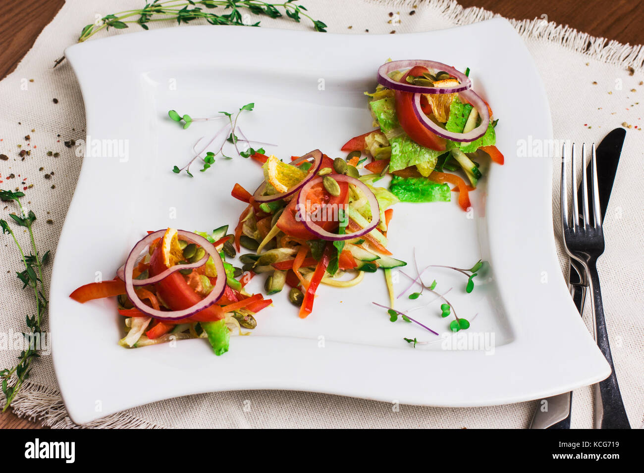 Salad of tomatoes, peppers, greens, oranges with pumpkin seeds on the white square plate - Stock Image