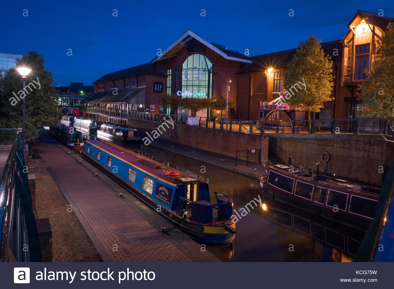 Canal boats moored on the Oxford Canal at Castle Quay Shopping Centre Banbury Oxfordshire England at night - Stock Image