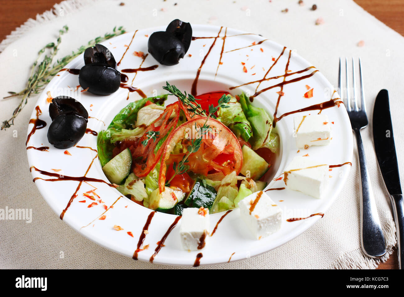 Greek salad in the white deep plate with the fork and knife - Stock Image