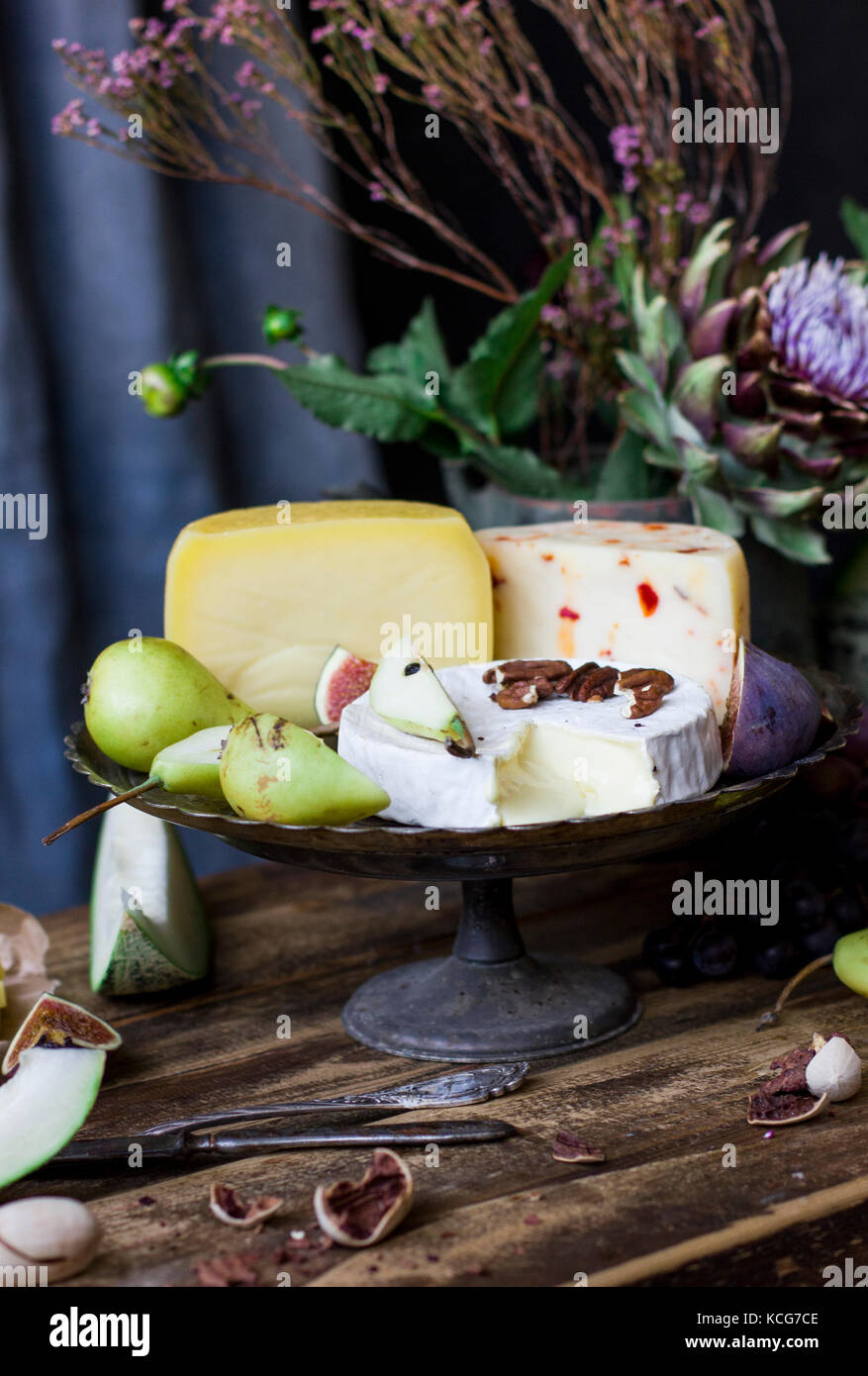 The different cheese, fresh fruit and garden flowers on old wood background - Stock Image