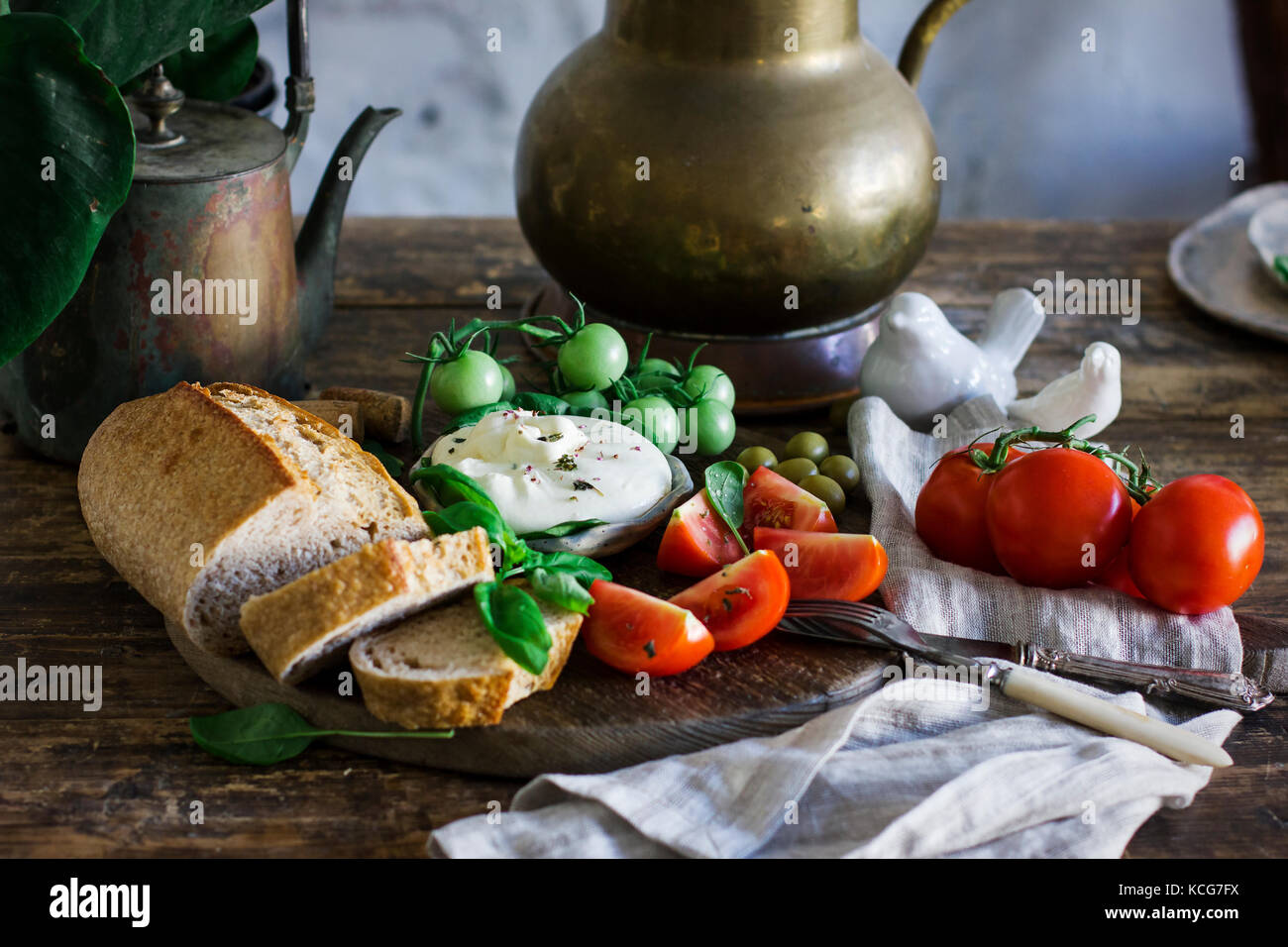 Fresh burrata cheese with tomatoes, Basil and multi-grain bread on the old wooden table. Vegetarian food - Stock Image