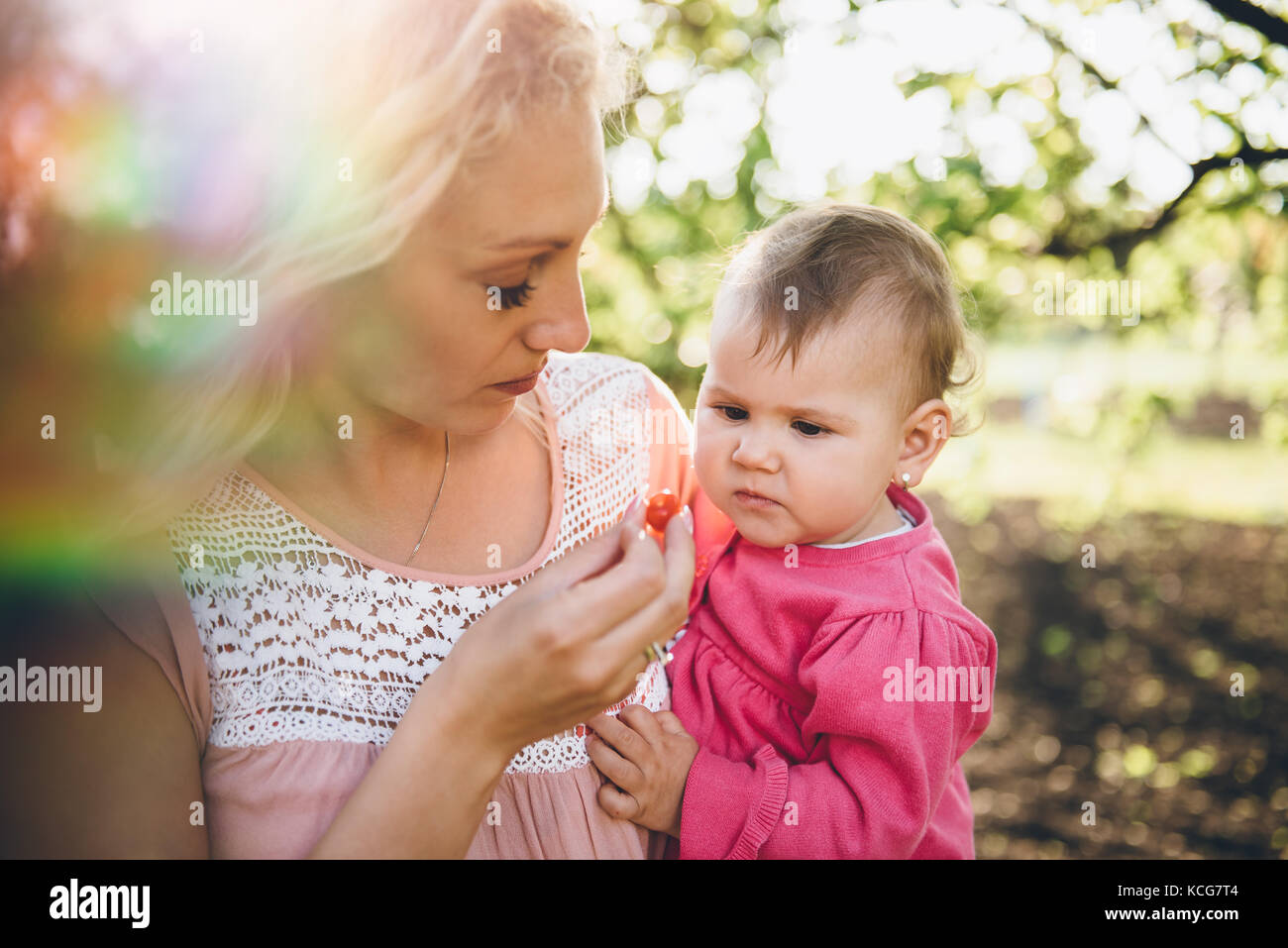Mother with baby Picking and eating Cherry In Garden - Stock Image