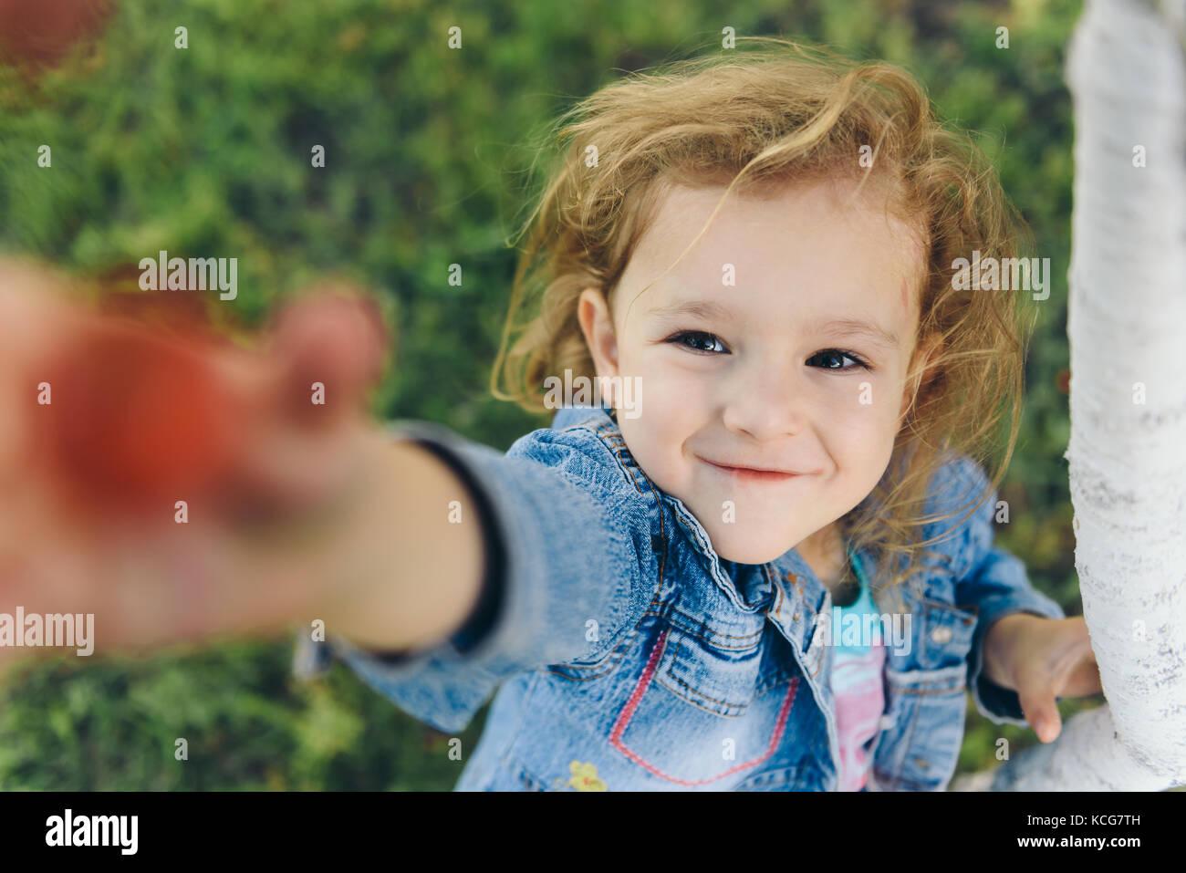 Happy little girl picking cherry in garden - Stock Image