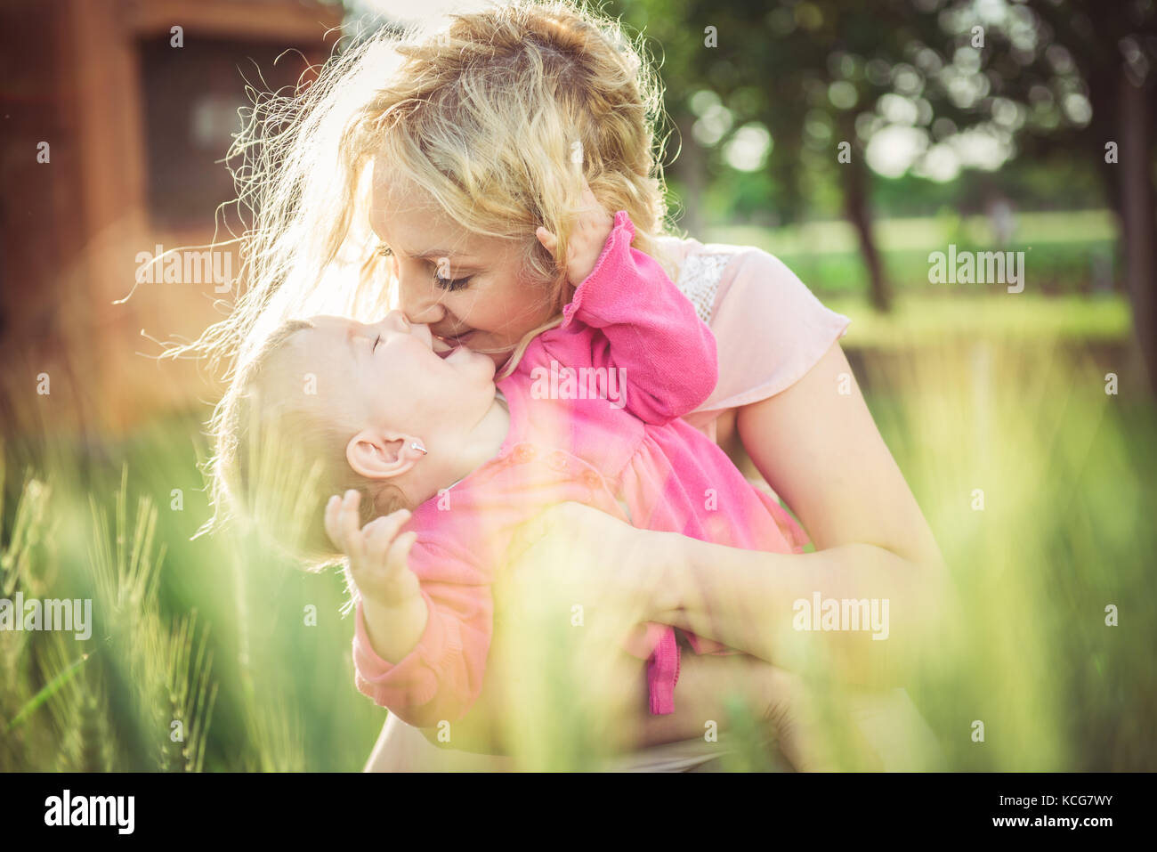 Young mother holding and kissing her baby in the grass - Stock Image