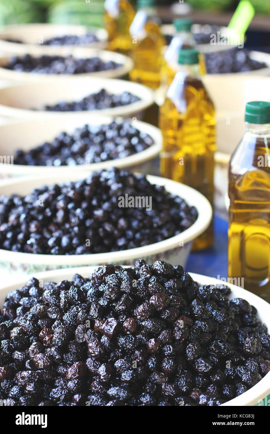 Black pickle olives in bowls and bottles with olive oil at the eastern market - Stock Image
